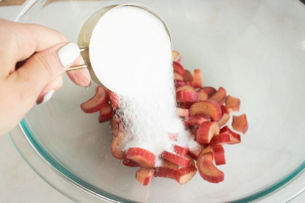 a lady's hand pouring a measuring cup of sugar into a glass bowl of sliced rhubarb
