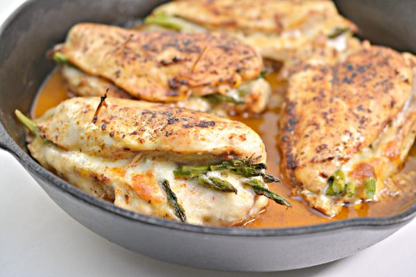 asparagus stuffed chicken being cooked in a skillet