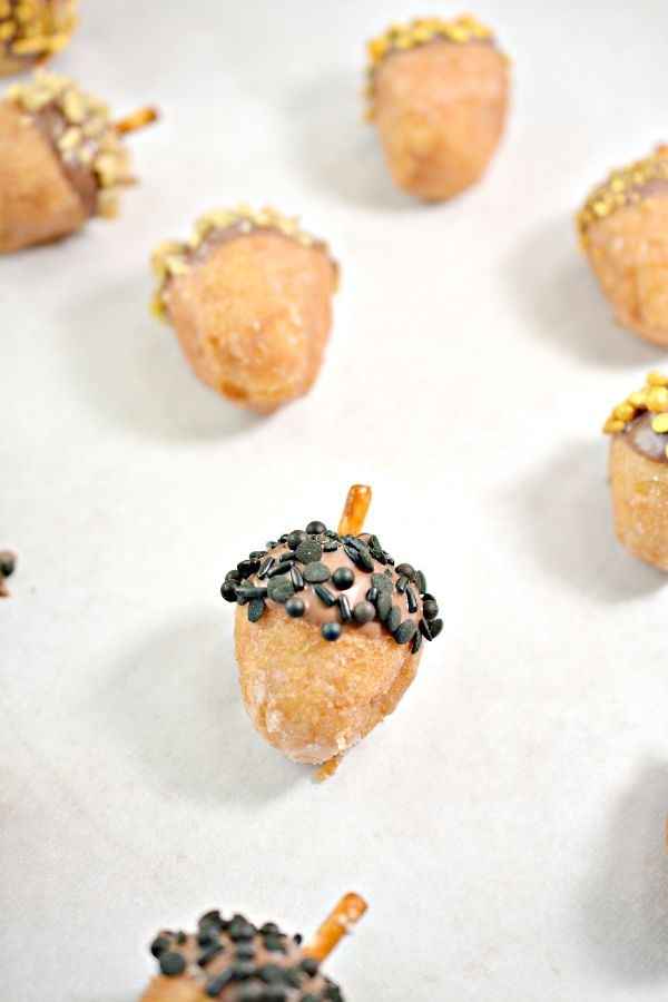 donut holes in the shape of acorns dipped in sprinkles on parchment paper
