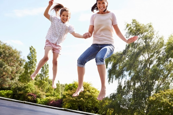 mom and daughter jumping on trampoline outdoors