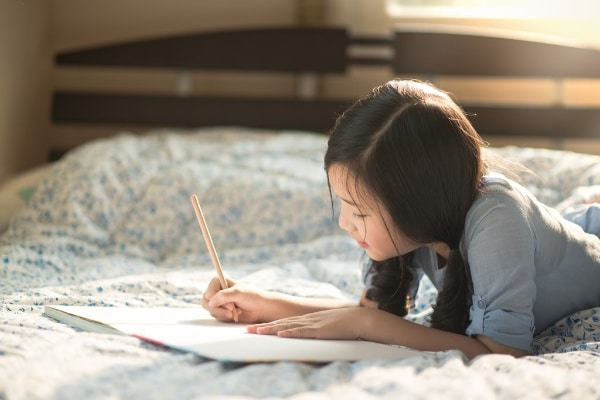a girl laying on a bed holding a pencil writing in a book