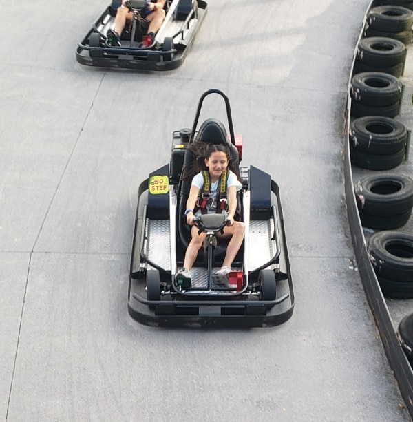 a girl driving a go-kart with another person behind her driving another go-kart on a track with tires next to them