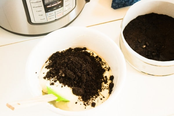 crushed oreos being folded into cheesecake batter by a spatula next to a bowl of crushed oreos and an instant pot
