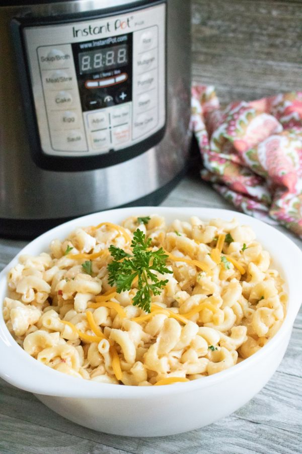 mac and cheese topped with parsley in a white bowl on a table next to an instant pot