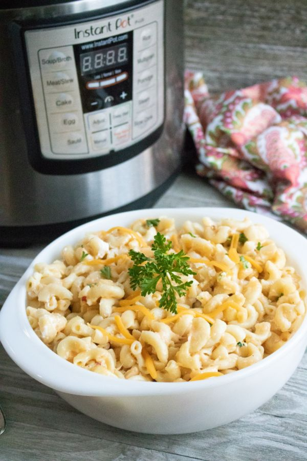 a white bowl of mac and cheese topped with parsley on a brown table next to an instant pot