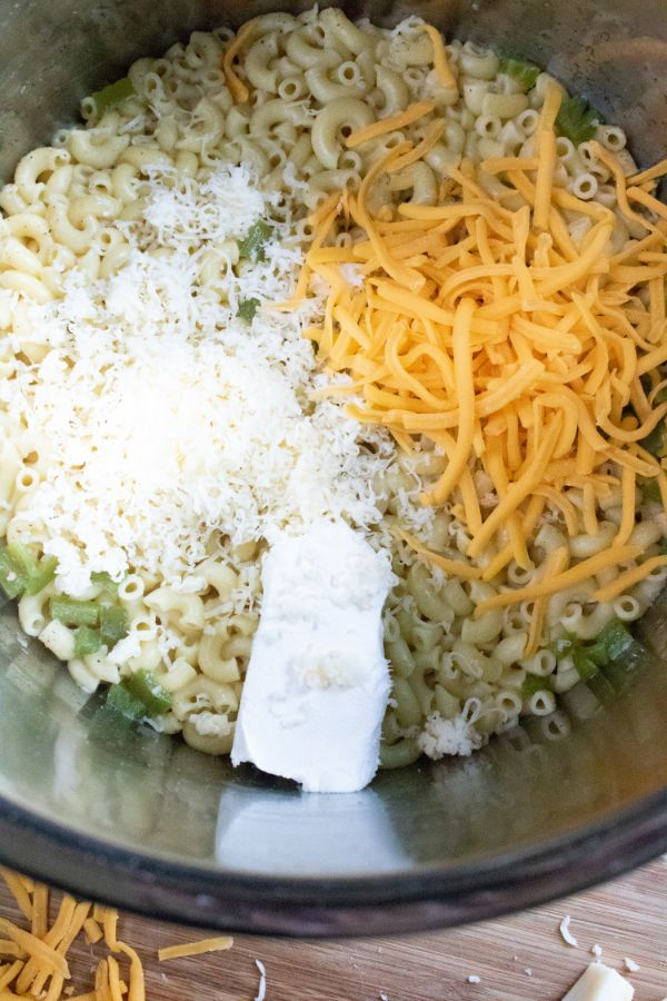 an instant pot filled with cooked elbow noodles and 3 different kinds of cheese