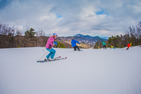 a family skiing on a snow covered mountain