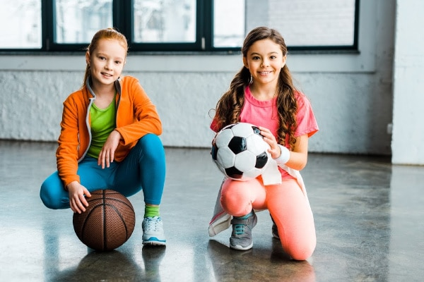 two girls kneeling down with a basketball and a soccer ball