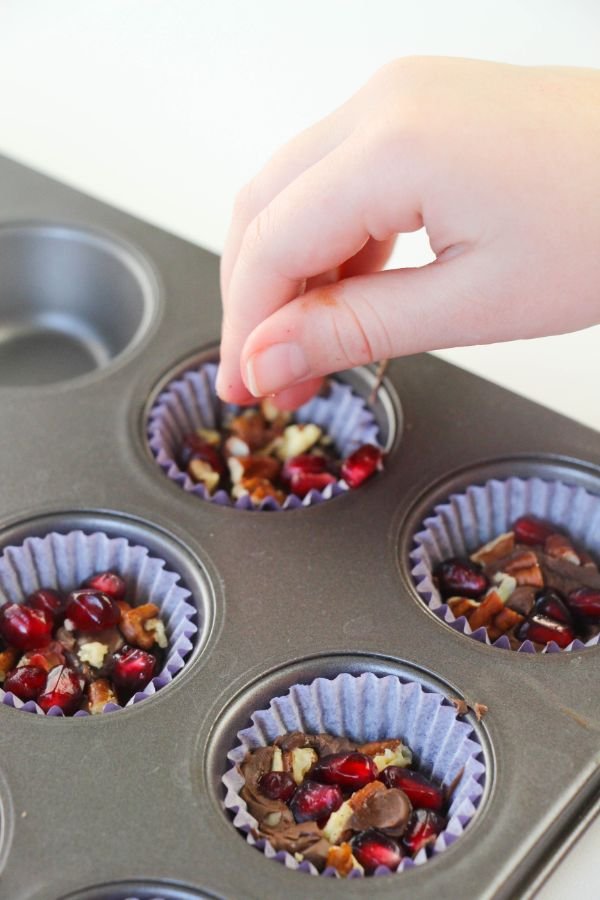 a person's hand sprinkling nuts and seeds on the pomegranate chocolate candy cups in a muffin tin
