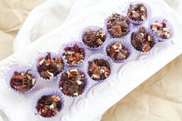 pomegranate chocolate candy cups in a muffin tin on a brown background