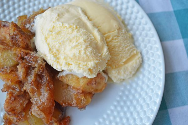 apple crisp topped with vanilla ice cream on a white plate on top of a blue and white checkered linen