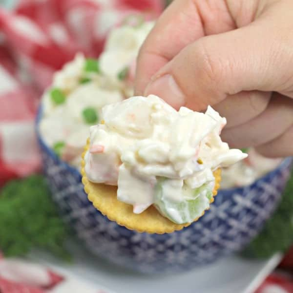 a hand holding a cracker with crab dip on it with a blue bowl of crab dip in the background