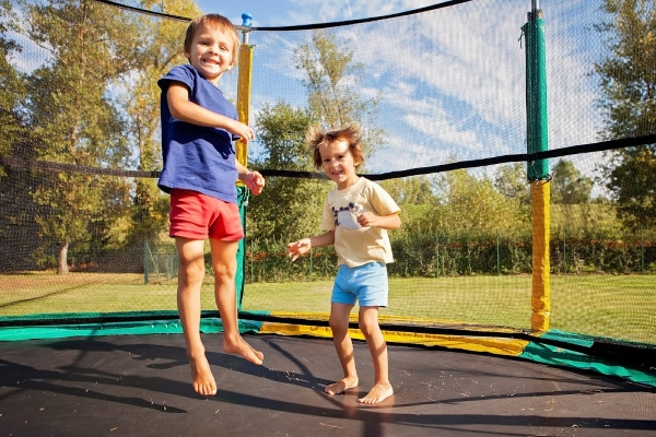 kids jumping on trampoline surrounded by safety net