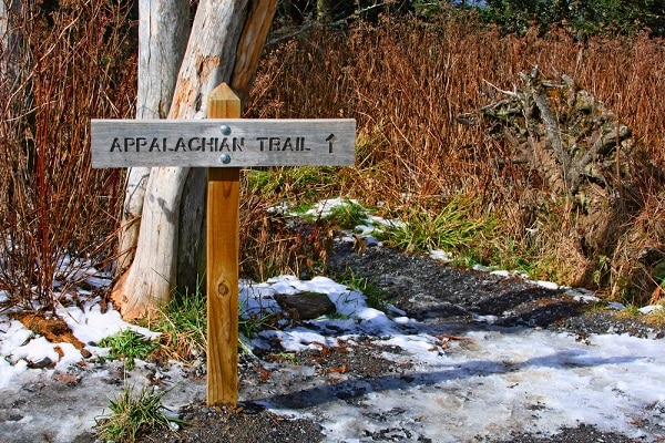 a sign that reads Appalachian Trail with a tree behind it and a snowy ground below it