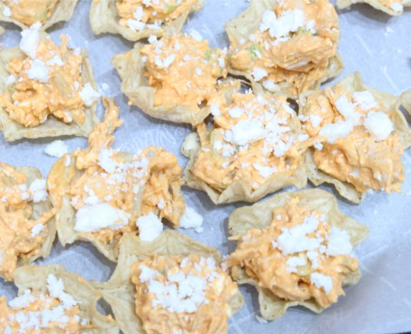buffalo chicken mixture on tortilla chips on a white table