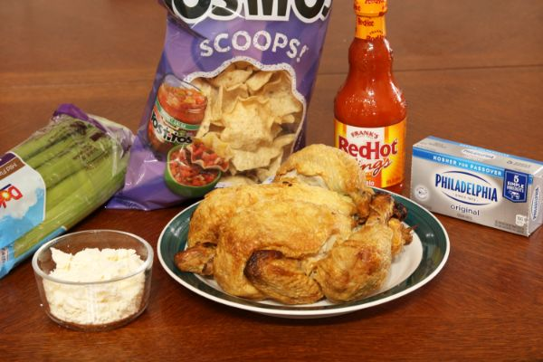 chicken on a plate next to blue cheese, celery, tortilla chips, hot sauce, and cream cheese all on a brown table
