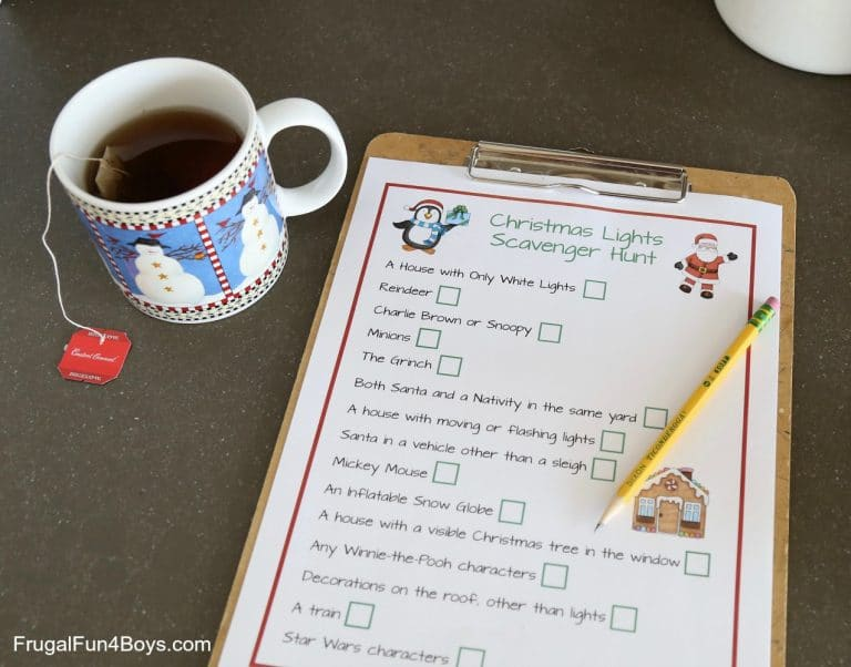 printable christmas lights scavenger hunt on a clipboard with a pencil on it on a brown table next to a snowman cup of tea
