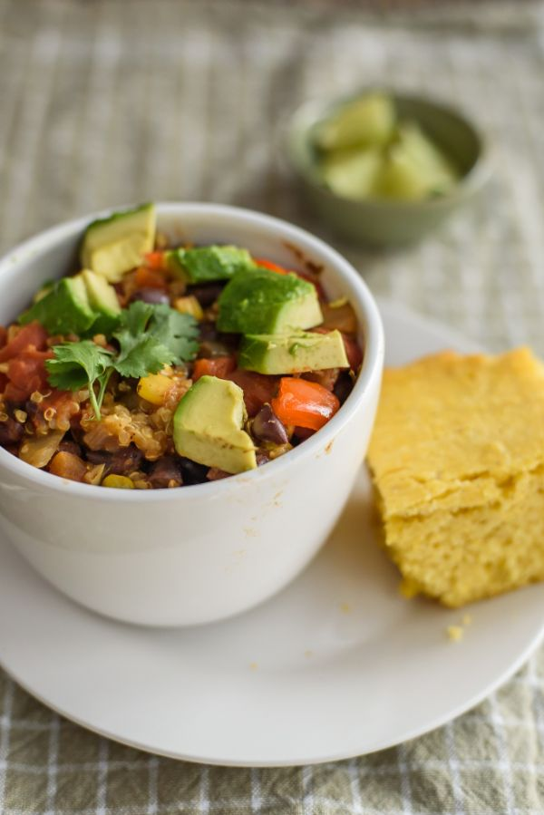 crockpot vegetarian chili topped with chopped avocado in a white bowl on a plate with cornbread next to it on a brown linen