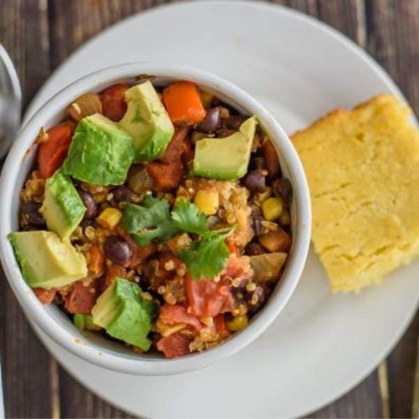 a top view of vegetarian chili topped with chopped avocado in a white bowl on a white plate with a piece of cornbread next to it