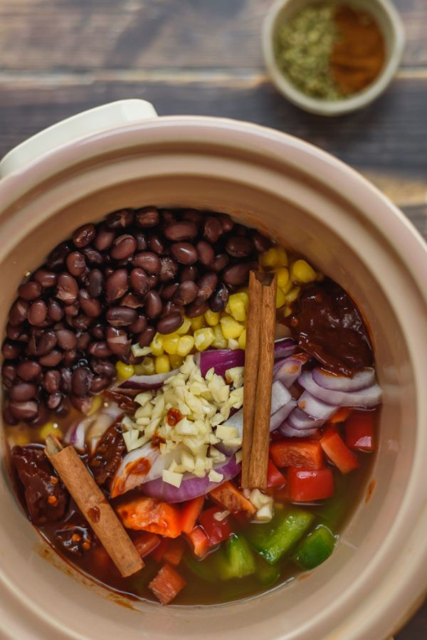 a top view of beans, corn, garlic, onions, tomatoes, bell pepper in a crockpot