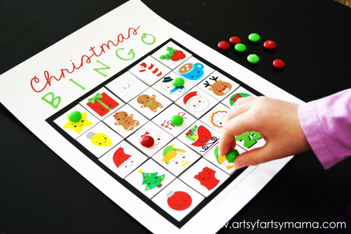 printable christmas bingon with a child's hand placing an m&m on it with more m&ms on the black background