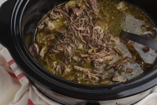 a crockpot with shredded meat in it being stirred by a spoon