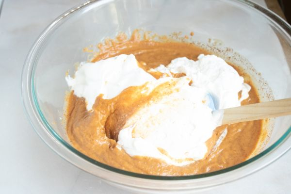 pumpkin mousse in a glass bowl topped with whipped cream with a spoon in it