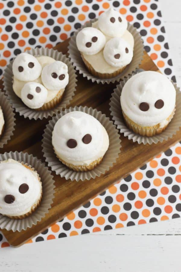 top view of cupcakes with white frosting topped with white meringue cookies with chocolate chips to look like ghosts on a black and orange dot paper