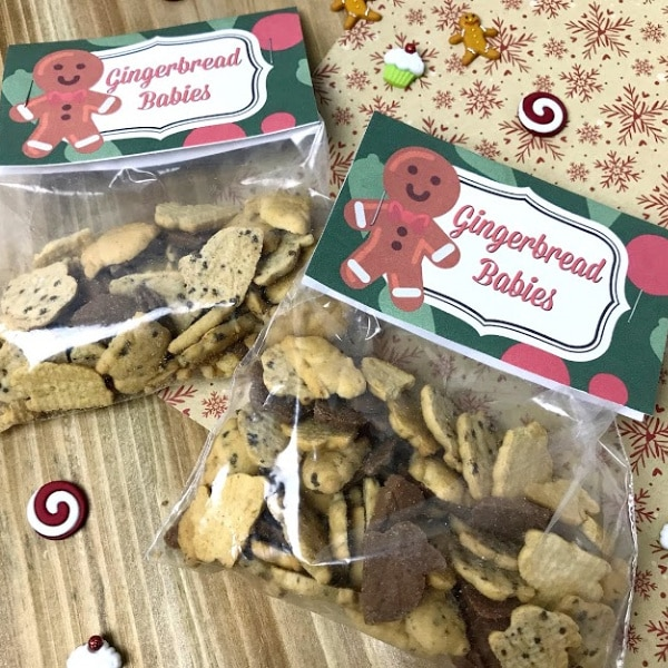 plastic bags filled with teddy grahams with printed labels that read gingerbread babies with a gingerbread man on them on a snowflake linen