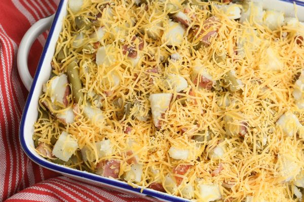 green bean potato casserole topped with cheese in a white casserole dish on a red linen