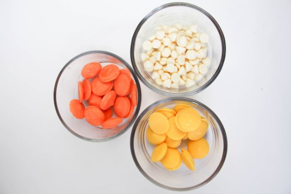 3 glass bowls filled with orange and yellow candy melts and white chocolate chips on a white background