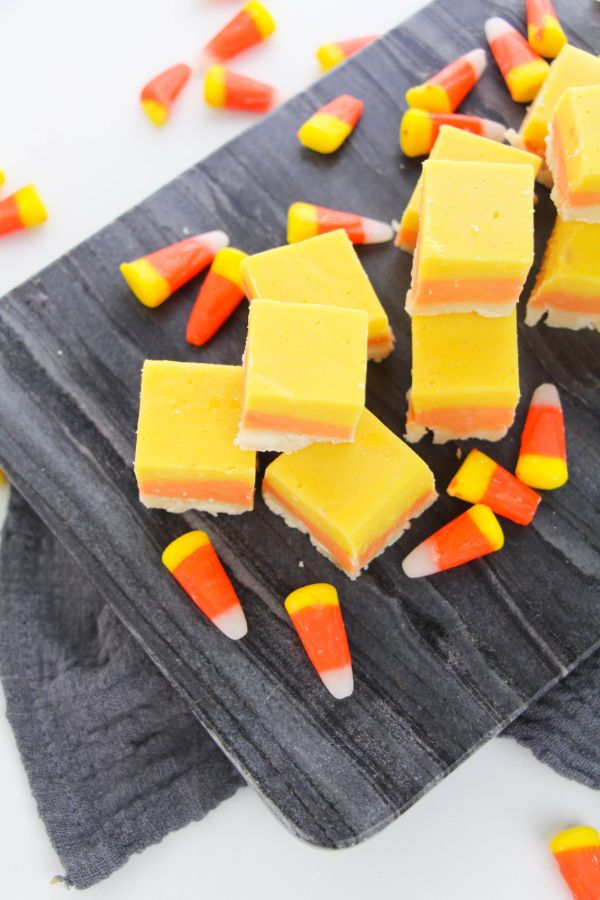 yellow, orange, and white Halloween fudge surrounded by candy corn on a wooden board