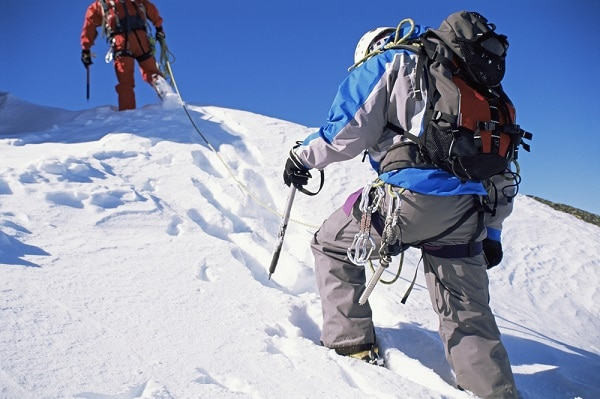 two mountain climbers climbing up a snow topped mountain
