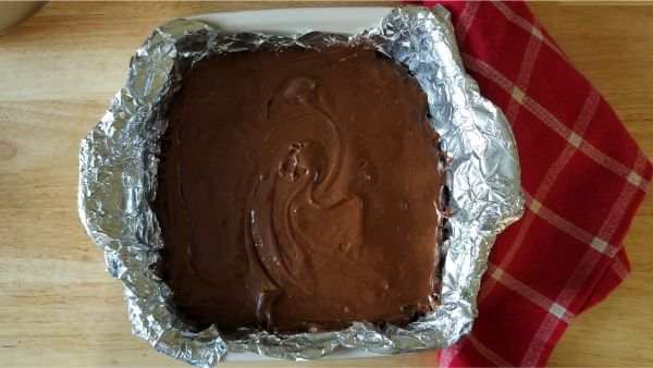 Reese's Peanut Butter Fudge in a baking pan covered with aluminum foil on a red linen on a brown table