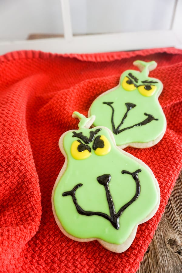 cookies in the shape of the Grinch, frosted with green, black and yellow frosting to look like the Grinch on a red linen on a wood table