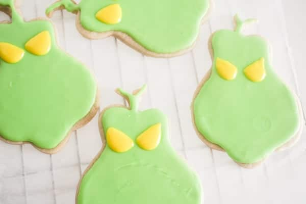 a cookie shaped like the Grinch with green frosting and yellow frosting on that to look like eyes