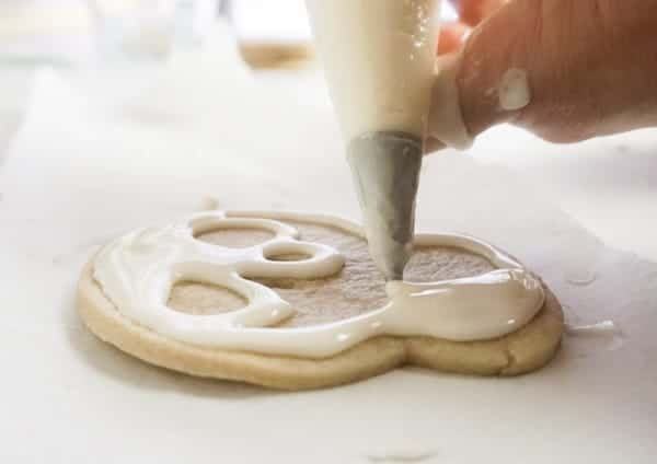 piping the white icing on a skull shaped cookie to look like Jack Skellington, cookie is on parchment paper