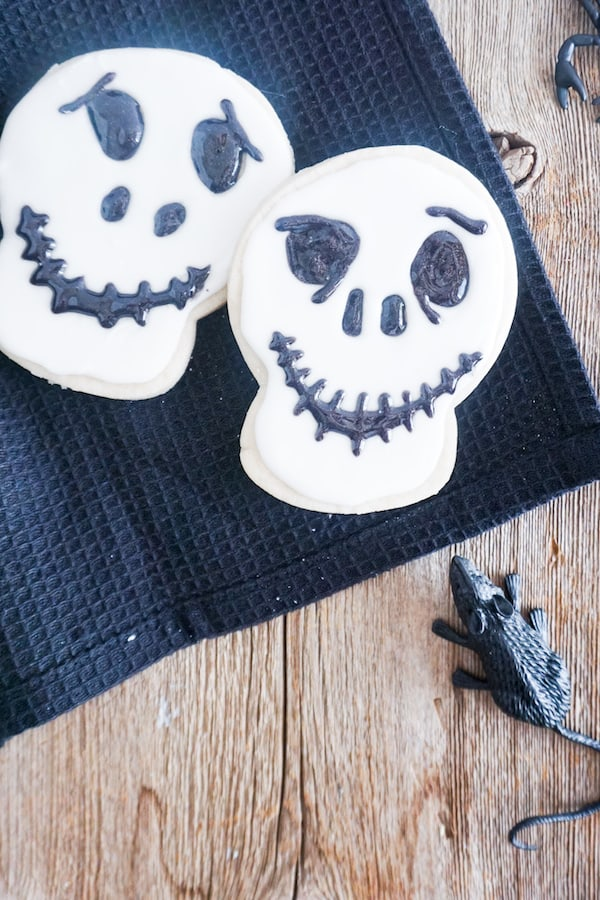 two cookies decorated with white frosting and black gel to look like Jack Skellington on a black linen on a wood table with a fake mouse next to it