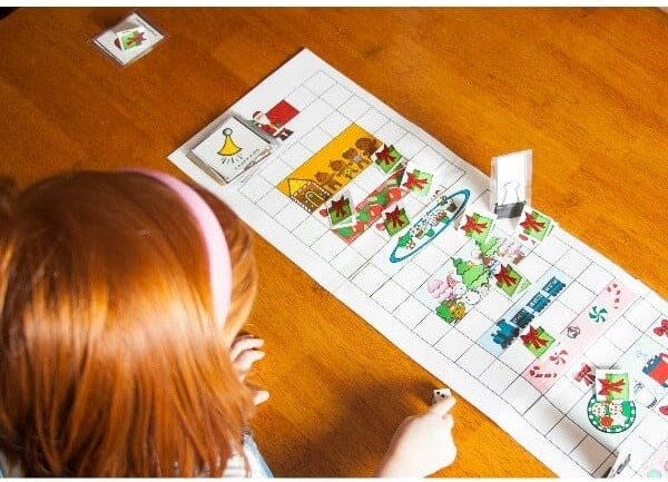 a red head girl looking at a printable christmas north pole mix up game on a table