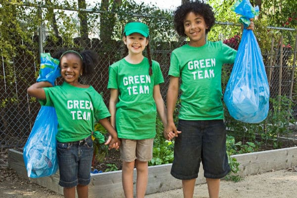 3 young children wearing green shirts and volunteering