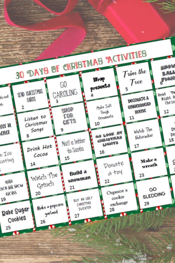 30 days of family Christmas activities printable on a brown table with a red ribbon and christmas tree leaves in the background