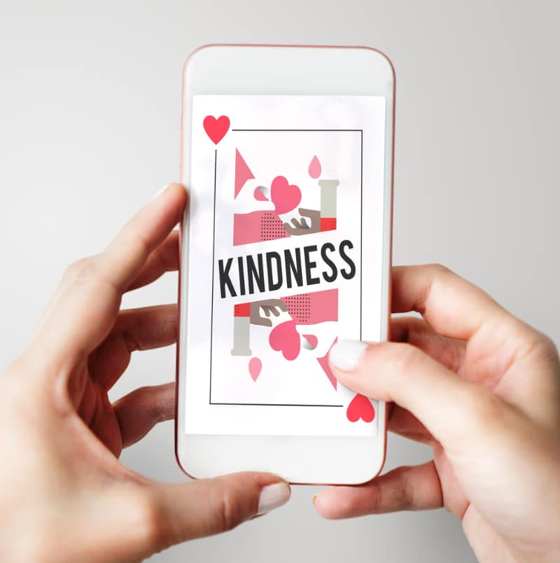 a woman's hands holding a phone with a hearts playing card with the word kindness on it
