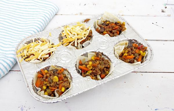 taco sausage cups a couple of them topped with cheese in a muffin tin on a white table with a blue and white striped linen next to it