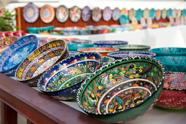 colorful bowls on a white and brown table with more bowls in the background on a fence
