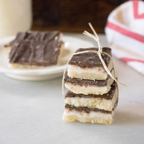 peppermint bars on table wrapped in a ribbon with peppermint bars on a plate in the background next to a red and white linen
