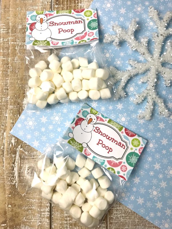 marshmallows in plastic bags labelled Snowman Poop on a brown and blue linen next to a snowflake