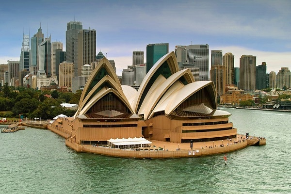 Sydney Opera House on the water with a city skyline in the background