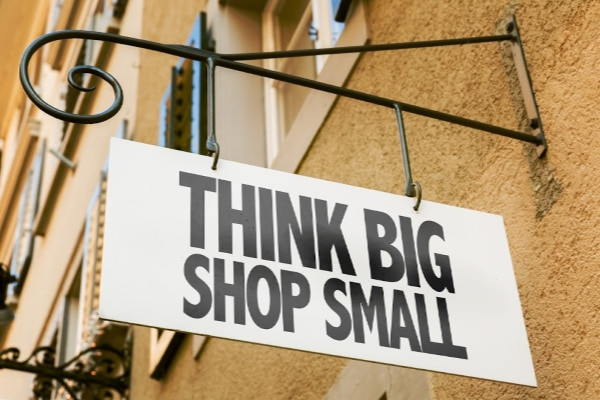 a sign on the side of the building with title text reading Think Big Shop Small
