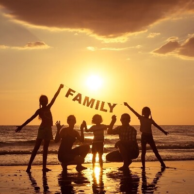 family standing on a beach taking a group portrait at sundown with a family sign