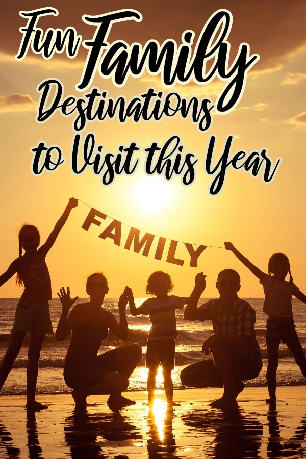 family standing on a beach taking a group portrait at sundown with a family sign with text which reads fun family destinations to visit this year